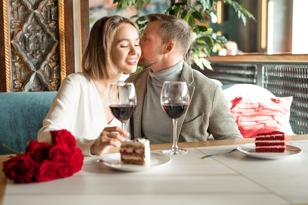 Young man whispering something to his girlfriend ear while both sitting by served table and having red wine and dessert in restaurant