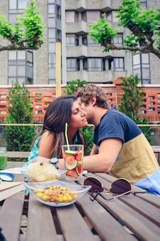 夏の日の屋外で健康的な飲み物や軽食とテーブルの周りに座っている美しい女性にささやく若い男