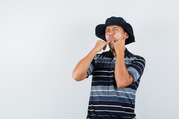 티셔츠, 모자 전면 보기에 손가락으로 휘파람을 부는 젊은 남자. 무료 사진