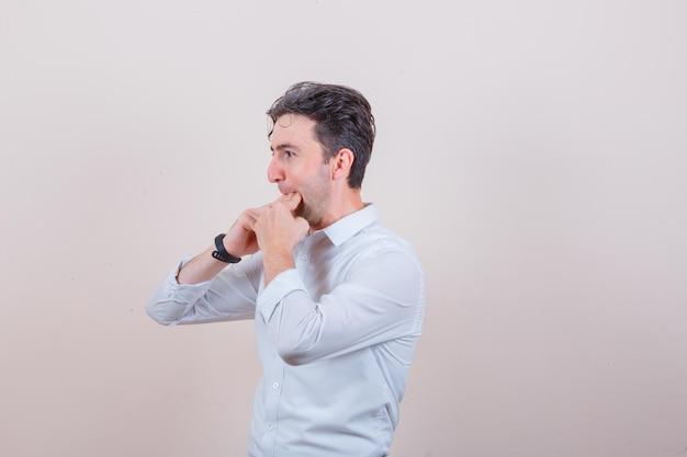 흰 셔츠에 손가락으로 휘파람을 불고 낙관적 인 찾고 젊은 남자