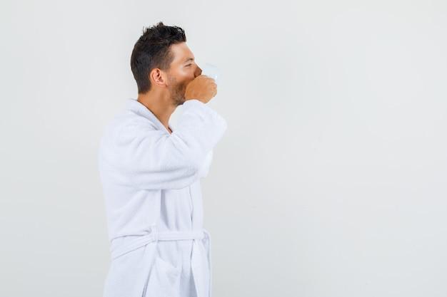 Giovane in accappatoio bianco che beve caffè dopo il bagno.