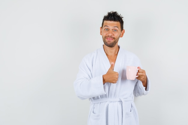Young man in white bathrobe holding cup of tea with thumb up and looking cheerful , front view.