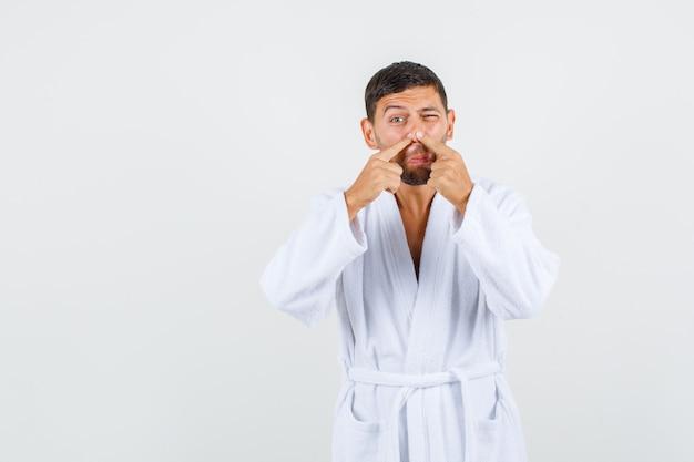 Giovane uomo in accappatoio bianco spremitura di acne sul naso, vista frontale.