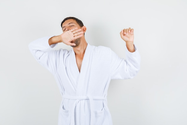 Young man in white bathrobe yawning and stretching and looking relaxed , front view.