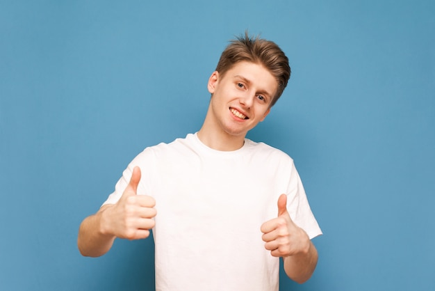 Young man in white blank t-shirt shows thumbs up, looks at camera and smiles.