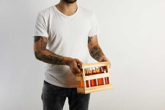 Young man in white cotton t-shirt with tattoos holding a crate of artisan beer isolated on white