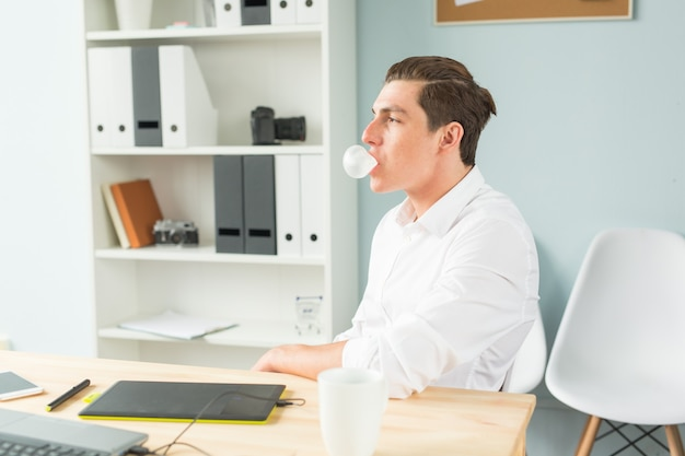 Young man in white shirt chewing gum