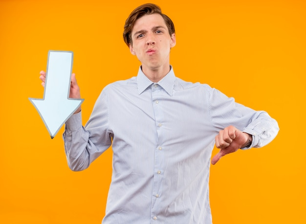 Young man in white shirt holding blue arrow  displeased showing thumb down standing over orange wall