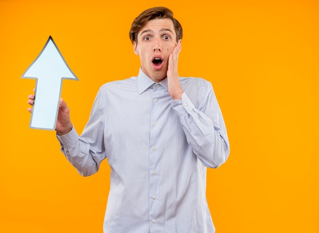 Young man in white shirt holding blue arrow looking at camera amazed and suprised standing over orange background