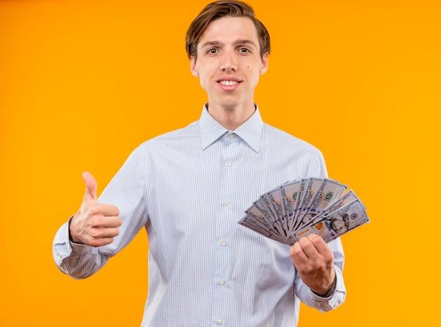Giovane uomo in camicia bianca tenendo in contanti guardando la telecamera sorridente fiducioso che mostra i pollici in su in piedi su sfondo arancione