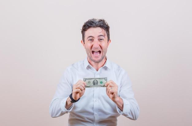Giovane in camicia bianca che tiene banconota da un dollaro e sembra fortunato