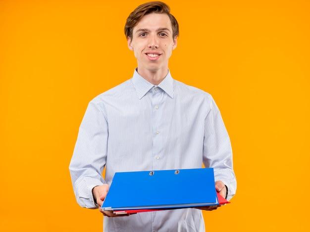 Giovane uomo in camicia bianca che tiene le cartelle che offrono loro guardando con il sorriso sul viso in piedi sopra la parete arancione