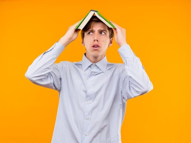 Giovane in camicia bianca che tiene libro aperto sopra la sua testa che osserva da parte in piedi spaventato sopra la parete arancione