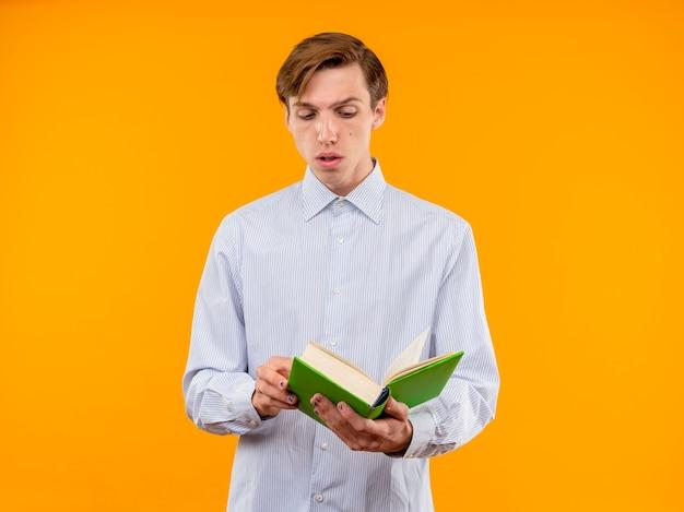 Giovane uomo in camicia bianca che tiene libro aperto guardandolo con faccia seria in piedi sopra la parete arancione