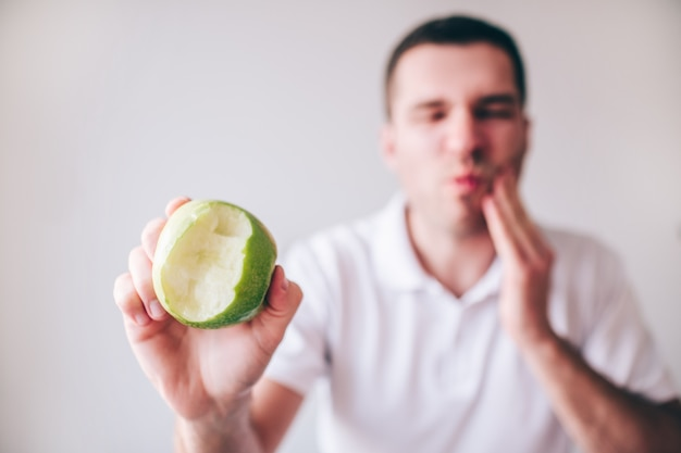 Young man in white shirt isolated over blurred defocused background. guy suffer from pain tooth pain and ache.