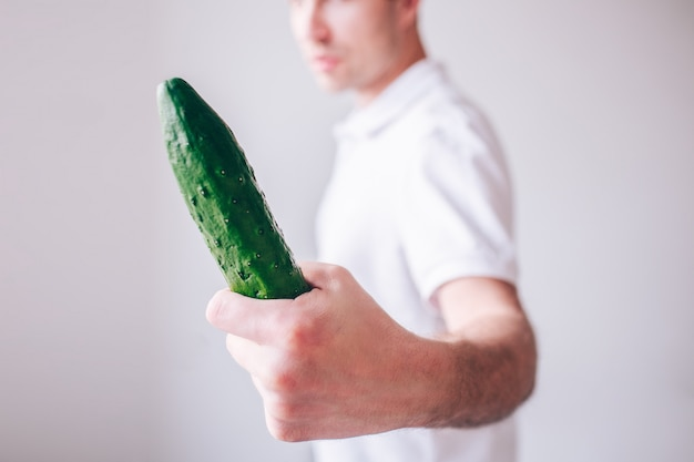 Young man in white shirt isolated over wall. guy look at long cucumber in hand. cut view blurred defocused wall.