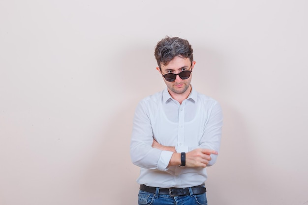 Young man in white shirt, jeans posing while looking over glasses and looking pensive