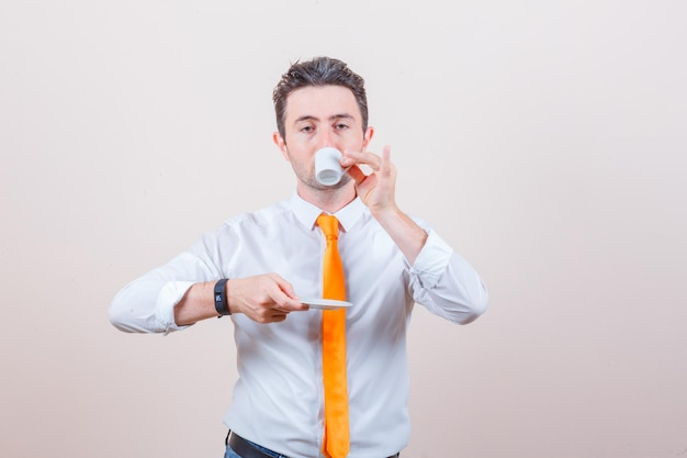 Young man in white shirt, tie drinking turkish coffee