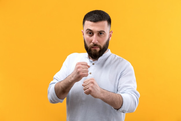 Young man in white shirt with beard getting on the fighting pose