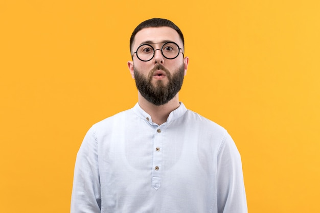 Young man in white shirt with beard and glasses with surprised expression