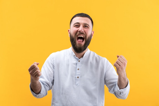 Young man in white shirt with beard posing