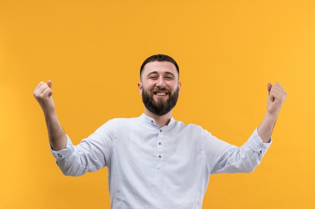 Young man in white shirt with beard with raised hands
