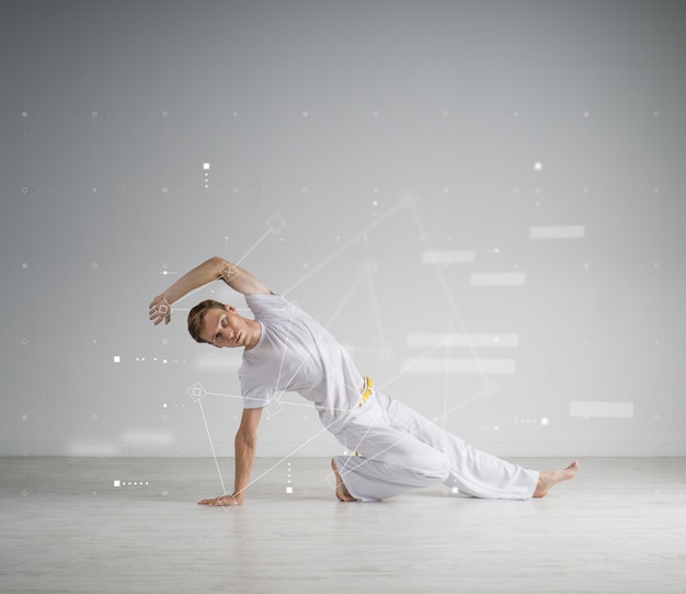 Young man in white sportswear performing a kick. indoor martial arts training, capoeira.