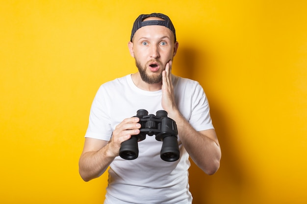 Young man in a white t-shirt and a baseball cap, surprised and shocked holds binoculars .