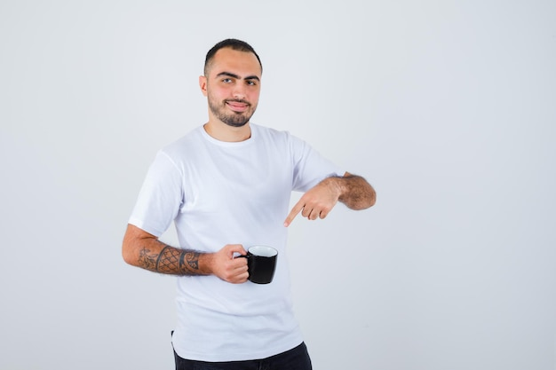 Young man in white t-shirt and black pants holding cup of tea and pointing to it and looking happy