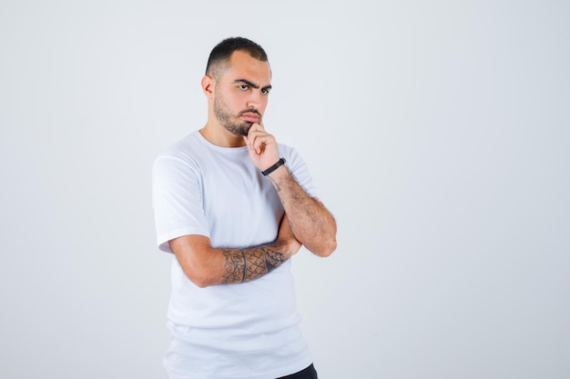 Young man in white t-shirt and black pants standing in thinking pose and looking pensive