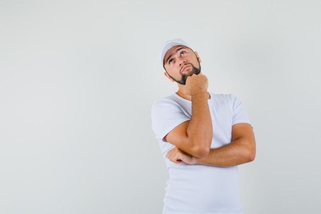Giovane uomo in maglietta bianca, berretto che guarda lontano mentre si tiene il pugno sulla mascella e guardando pensieroso, vista frontale.
