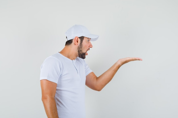 Young man in white t-shirt,cap raising hand in questioning gesture aside and looking serious .