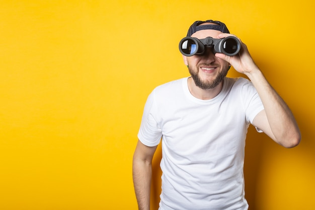 Young man in a white t-shirt delighted in shock looks in surprise with binoculars