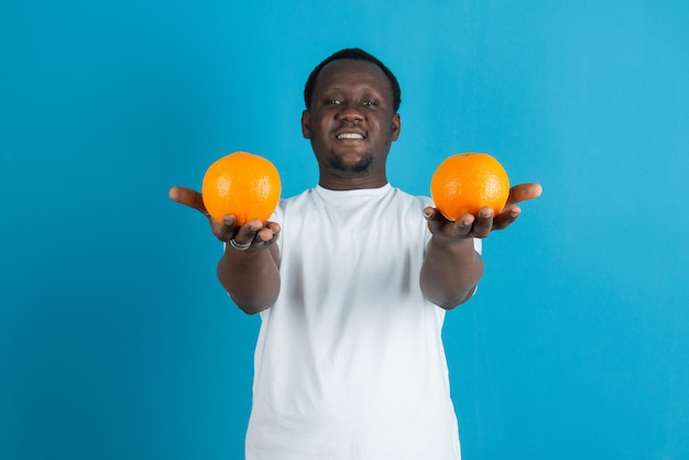 Young man in white t-shirt holding two sweet orange fruits against blue wall