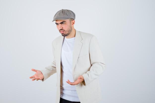 Giovane con maglietta bianca, giacca e berretto grigio che allunga una mano come se tenesse qualcosa e sembri serio