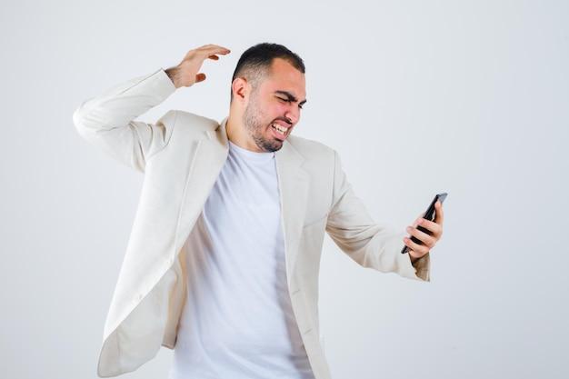 Giovane uomo in maglietta bianca, giacca che tiene il telefono cellulare e lo guarda e sembra furioso, vista frontale.