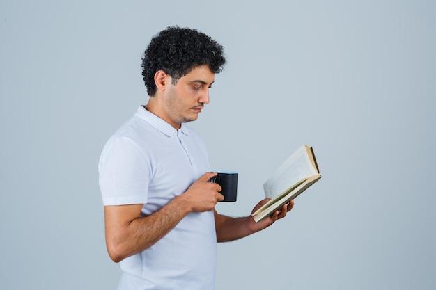 Giovane in maglietta bianca e jeans che beve una tazza di tè mentre legge il libro e sembra concentrato, vista frontale.