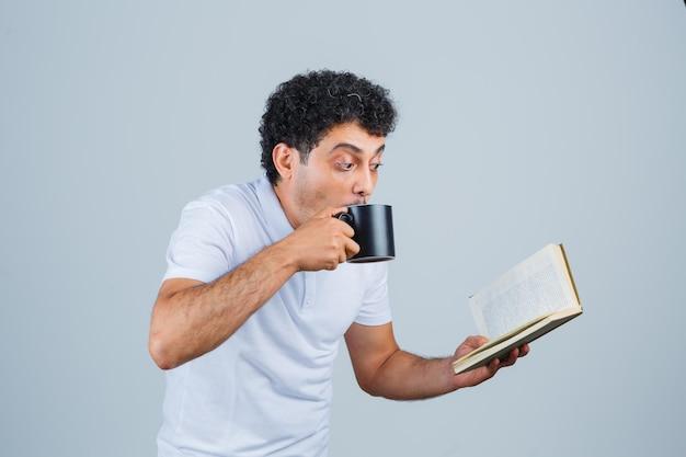 Giovane in maglietta bianca e jeans che beve una tazza di tè mentre legge il libro e sembra felice, vista frontale.