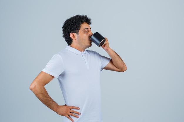 Giovane uomo in maglietta bianca e jeans che tiene la mano sulla vita mentre beve una tazza di tè e sembra assetato, vista frontale.