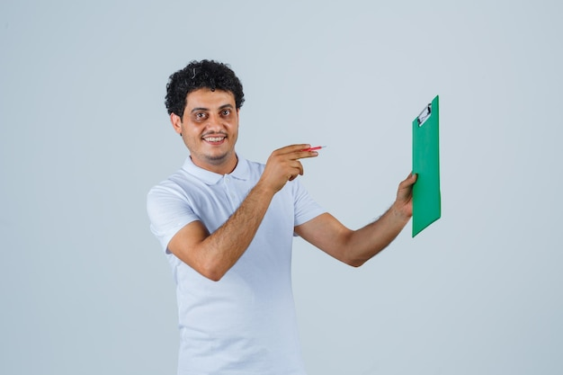 Young man in white t-shirt and jeans holding notebook and pointing to it with pen, looking at camera and looking happy , front view.