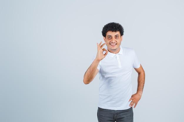 Giovane in maglietta bianca e jeans che mostrano segno ok mentre si tiene la mano sulla vita e sembra felice, vista frontale.