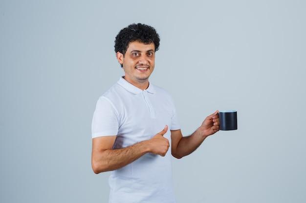 Giovane in maglietta bianca e jeans che mostra pollice in su e tiene in mano una tazza di tè e sembra felice, vista frontale.
