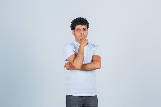Giovane uomo in maglietta bianca e jeans in piedi in posa di pensiero, mento appoggiato a portata di mano e sguardo pensieroso, vista frontale.