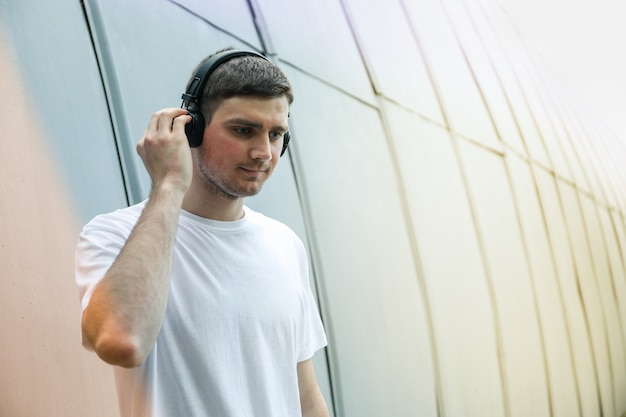 Young man in white t-shirt listening to music in headphones