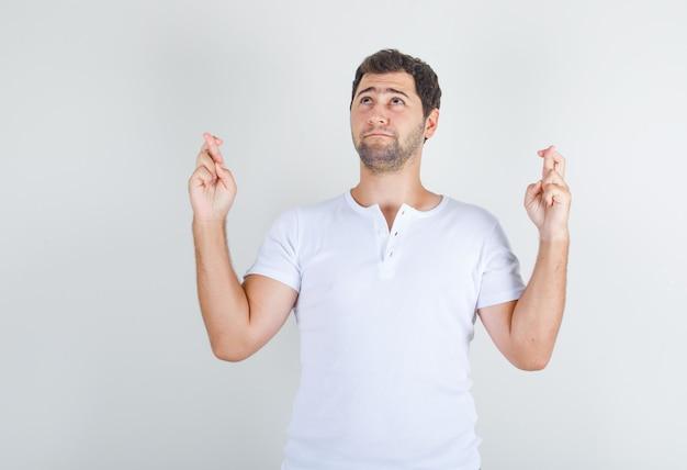 Giovane in maglietta bianca che osserva in su con le dita incrociate e che sembra speranzoso