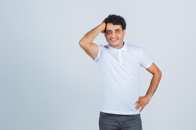 Giovane in maglietta bianca, pantaloni in posa con la mano sulla testa e guardando fiducioso, vista frontale.