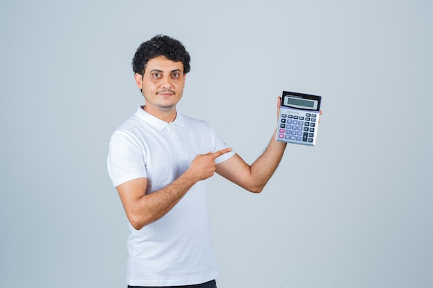 Young man in white t-shirt pointing at calculator and looking confident , front view.