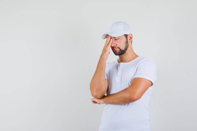 Giovane uomo in maglietta bianca strofinando la fronte e guardando assonnato, vista frontale. spazio libero per il testo
