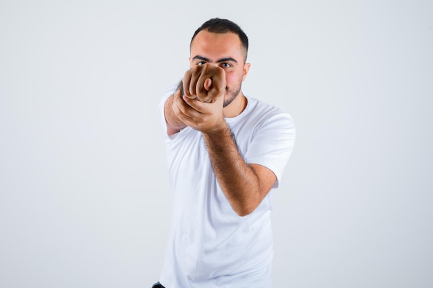 Giovane uomo in maglietta bianca che mostra il segno del fico e sembra maleducato