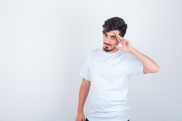 Young man in white t-shirt showing salute gesture and looking confident
